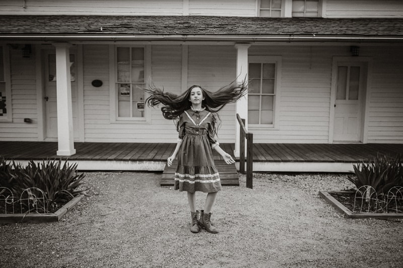 Denver Fine Art Photography, black and white image of girl in dress outside of old home
