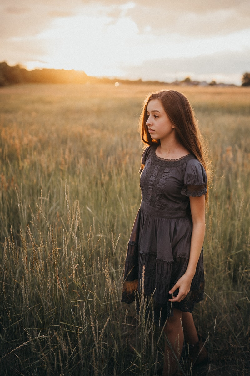 Denver Children's Photography, girl in dark blue dress standing in a field at sunset