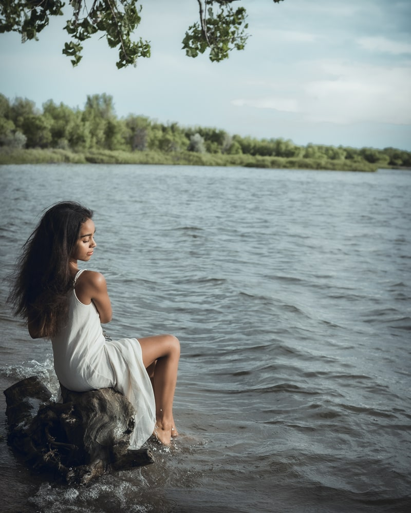 Denver Children's Photography, girl in white dress sitting with her feet in the lake