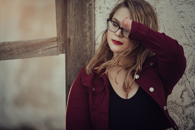 Denver Senior Photography, girl leaning against wall, wiping her hair from her face