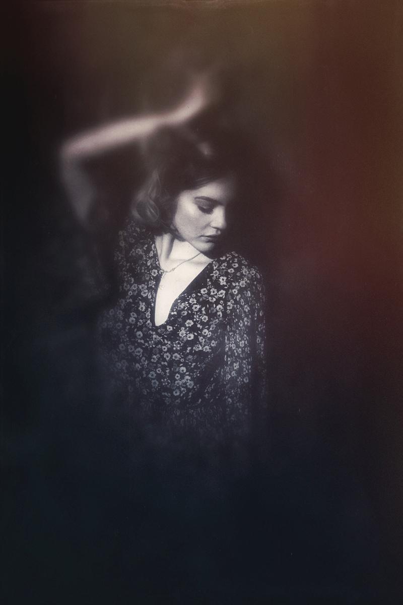 Denver Senior Photography, artistically edited girl leaning against a dark background