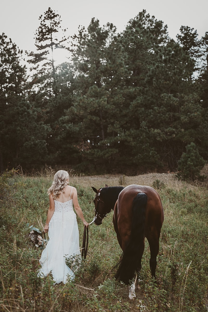Denver Bridal Photography, bride walking through tall grass with a horse