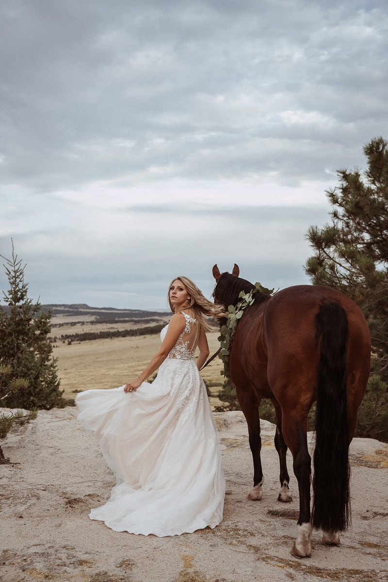Denver Bridal Photography, bride walking away with horse, looking over her shoulder