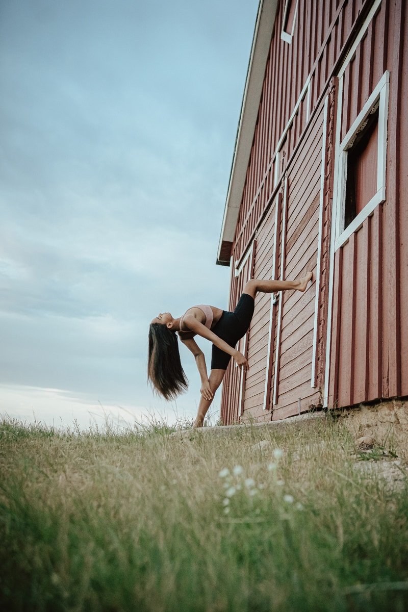 Denver Dance Photography, girl posing with leg up on a barn